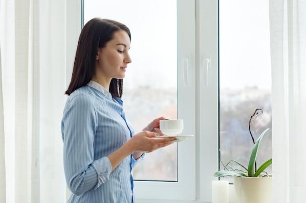 Jonge mooie vrouw permanent thuis in de buurt van venster met kopje koffie, winterseizoen ruimte, lichte gordijnen, kopie ruimte