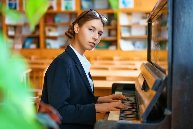 Jonge mooie vrouw piano spelen in de klas