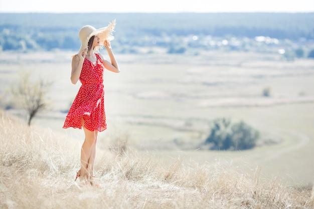Jonge mooie vrouw portret buitenshuis op sappige zomer of herfst vrouw op val tijd. dame op de aard die rode modieuze kleding draagt.
