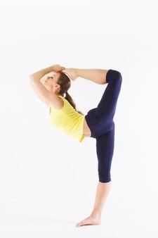 Jonge mooie vrouw poseren in een sportschool outfit. jong gezond meisje met een perfect figuur, geïsoleerd op een witte achtergrond