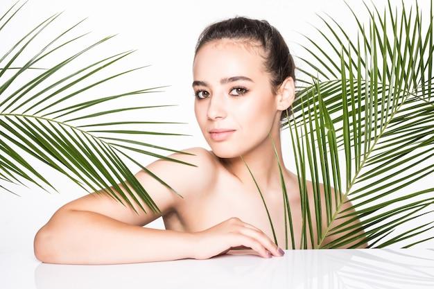 Jonge mooie vrouw poseren met groene palmbladeren