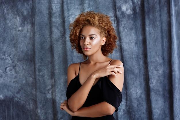 Jonge mooie vrouw poseren over grijze doek achtergrond