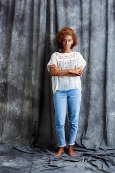 Jonge mooie vrouw poseren over grijze doek