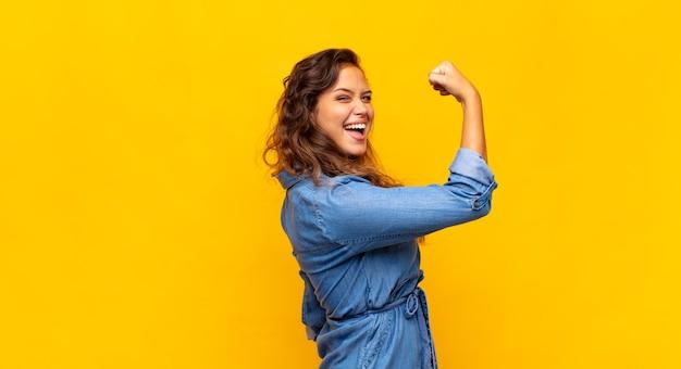 Jonge mooie vrouw poseren tegen de gekleurde muur