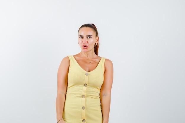Jonge mooie vrouw poseren terwijl staande met pruilende lippen in jurk en op zoek verrast. vooraanzicht.