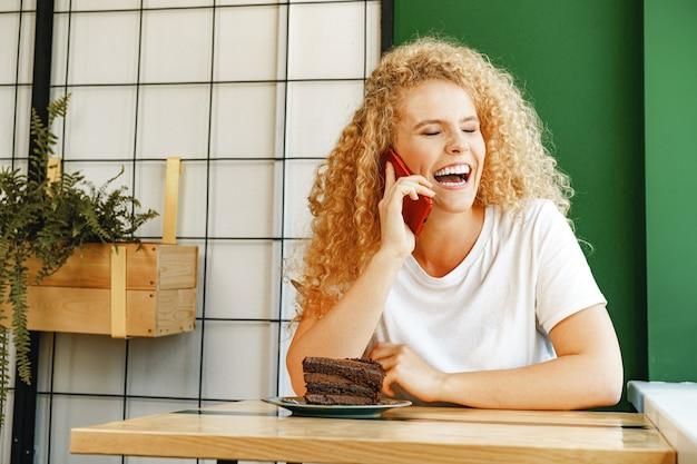 Jonge mooie vrouw praten aan de telefoon in cafetaria