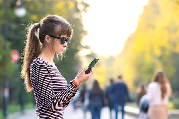 Jonge mooie vrouw praten op mobiele telefoon in warme zomerdag buitenshuis.
