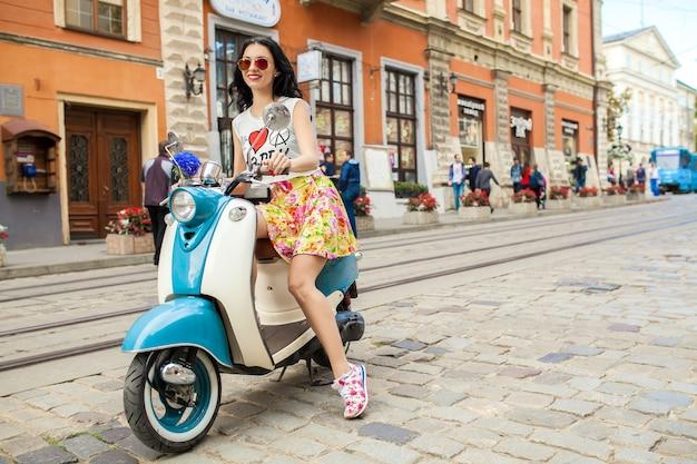 Jonge mooie vrouw rijden op motor stad straat