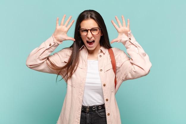 Jonge mooie vrouw schreeuwen in paniek of woede, geschokt, doodsbang of woedend, met handen naast hoofd. studentenconcept