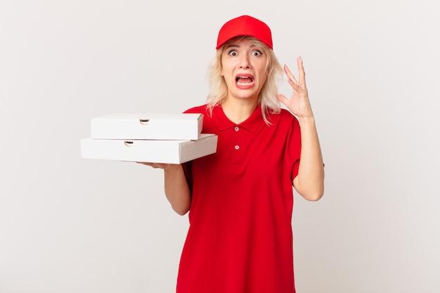 Jonge mooie vrouw schreeuwen met handen omhoog in de lucht. pizza bezorgconcept
