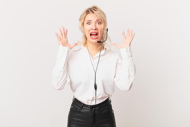 Jonge mooie vrouw schreeuwen met handen omhoog in de lucht. telemarketing concept