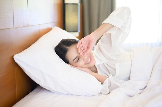 Jonge mooie vrouw slapen in haar bed thuis