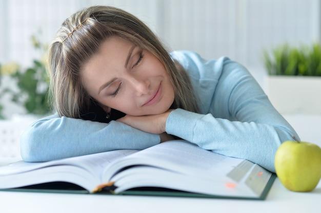 Jonge mooie vrouw slapen op een boek