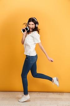 Jonge mooie vrouw springen dansen zingen met mobiele telefoon.