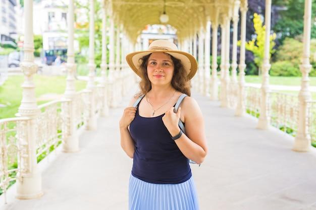 Jonge mooie vrouw staat in de prachtige witte colonnade in karlovy vary resort in tsjechië.