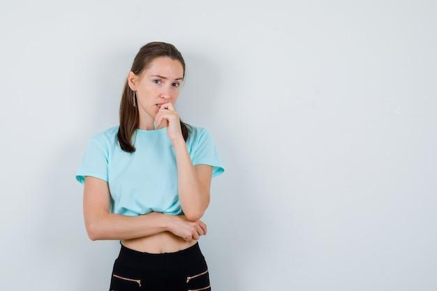 Jonge mooie vrouw staat in denkende pose in t-shirt en kijkt verbaasd, vooraanzicht.