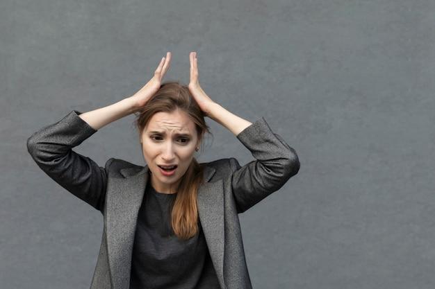 Jonge mooie vrouw staat in een grijs pak. de zakenvrouw is in paniek, ze heeft afschuw op haar gezicht.