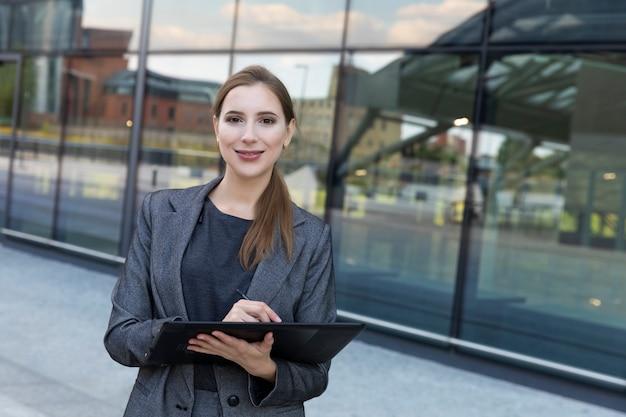 Jonge mooie vrouw staat in een pak op de muur van een kantoorgebouw. ze houdt een grafisch tablet in haar handen, voert de nodige gegevens in.