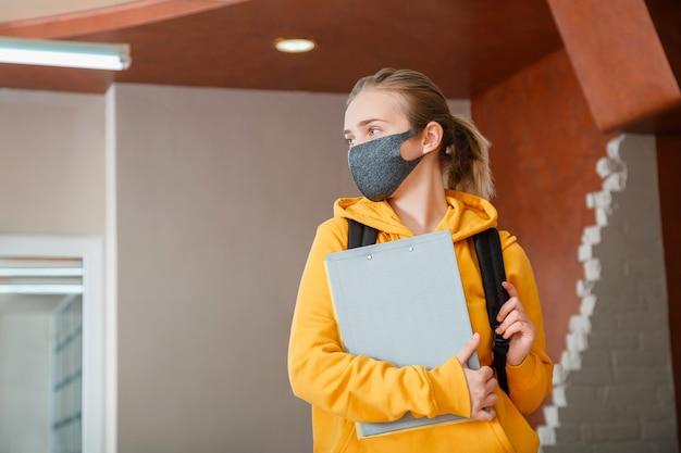 Jonge mooie vrouw student dragen beschermend masker met rugzak tiener meisje blonde kaukasische tiener reiziger in masker met notebooks gelukkige student in heropenen universiteitscampus covid lockdown