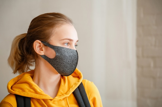 Jonge mooie vrouw student dragen beschermend masker portret met rugzak tiener meisje blonde