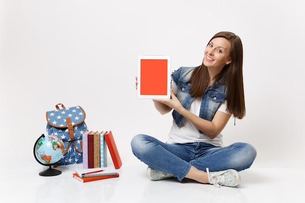 Jonge mooie vrouw student op zoek op tablet pc-computer met leeg zwart leeg scherm zit in de buurt van globe rugzak, schoolboeken geïsoleerd