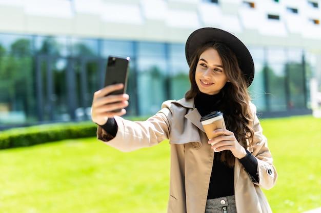 Jonge mooie vrouw student slijtage in jas en hoed koffie te houden om te gaan nemen selfie aan de telefoon in de straat