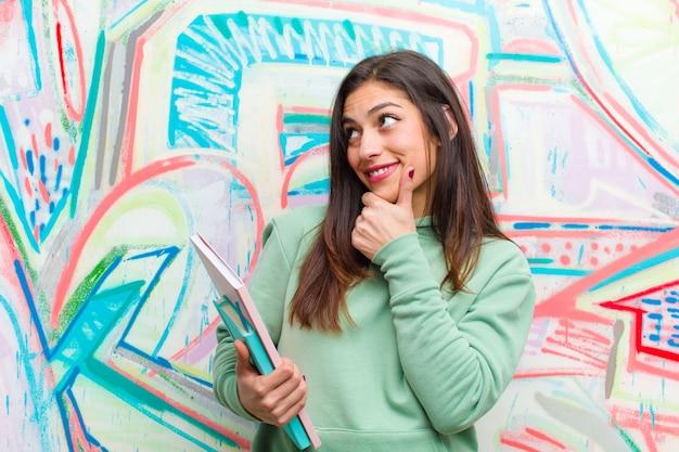 Jonge mooie vrouw tegen graffitimuur