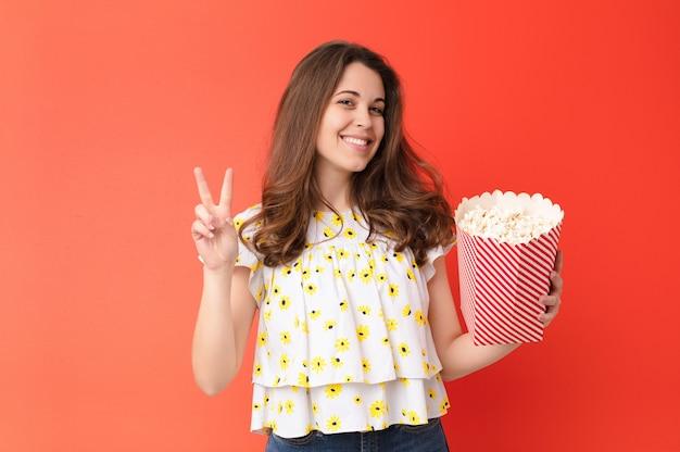 Jonge mooie vrouw tegen rode muur met een popcornemmer