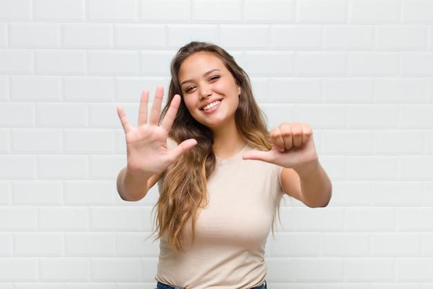 Jonge mooie vrouw tegen witte muur