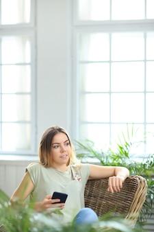 Jonge mooie vrouw thuis met planten