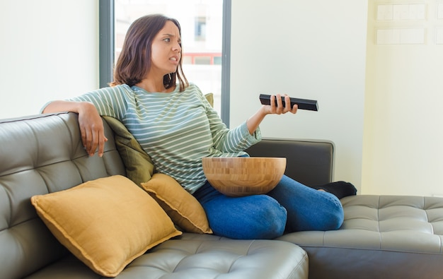 Jonge mooie vrouw thuis tv-kijken