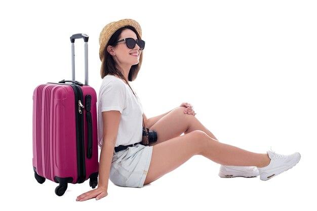 Jonge mooie vrouw toerist in stro hoed met koffer en camera geïsoleerd op een witte achtergrond