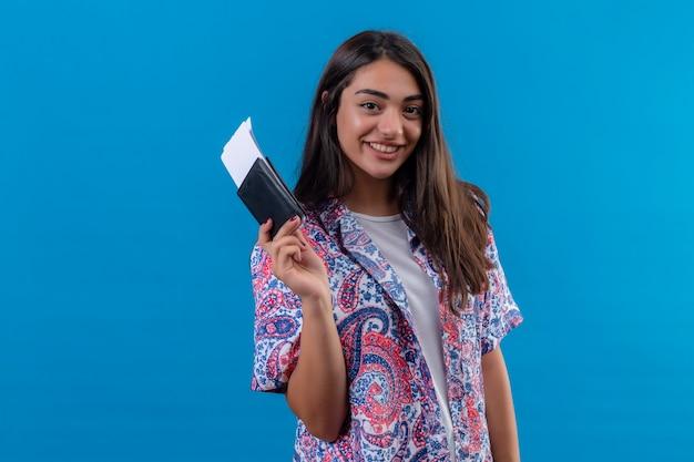 Jonge mooie vrouw toeristische bedrijf paspoort met kaartjes camera kijken met vertrouwen glimlach positief en gelukkig staande over verzadigde blauwe achtergrond