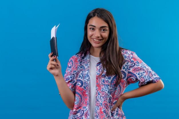 Jonge mooie vrouw toeristische bedrijf paspoort met kaartjes kijken camera glimlachend vrolijk positief en gelukkig klaar voor vakantie staande over geïsoleerde blauwe achtergrond