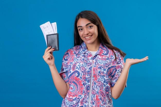 Jonge mooie vrouw toeristische bedrijf paspoort met kaartjes kijken camera glimlachend vrolijk presenteren met arm van de hand klaar voor vakantie staande over geïsoleerde blauwe achtergrond