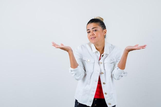 Jonge mooie vrouw toont hulpeloos gebaar in t-shirt, witte jas en kijkt verbijsterd, vooraanzicht.