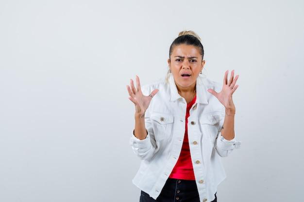 Jonge mooie vrouw toont overgave gebaar in t-shirt, witte jas en kijkt boos. vooraanzicht.