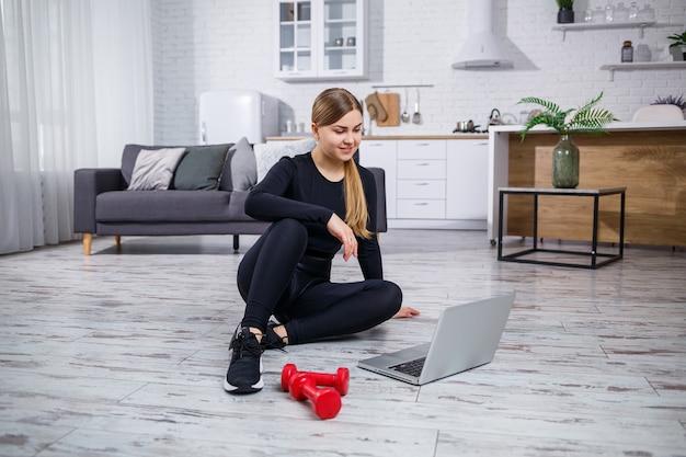 Jonge mooie vrouw trainer in een zwarte top en legging zit met een laptop en kijkt naar online training, fitness thuis tijdens quarantaine. gezonde levensstijl. halters liggen op de grond