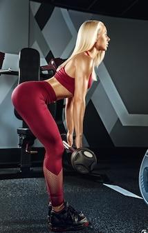 Jonge mooie vrouw training in de sportschool.