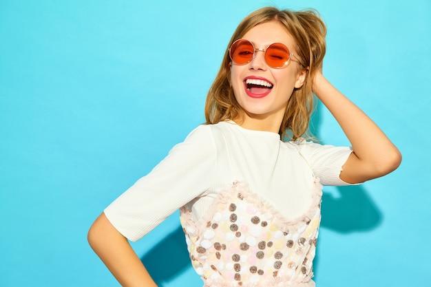Jonge mooie vrouw. trendy vrouw in casual zomer kleding in zonnebril. positieve vrouwelijke emotie gezichtsuitdrukking lichaamstaal. grappig model dat bij het blauwe muur knipogen wordt geïsoleerd