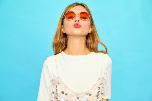 Jonge mooie vrouw. trendy vrouw in casual zomer kleding in zonnebril. positieve vrouwelijke emotie gezichtsuitdrukking lichaamstaal. grappig model dat op blauwe muur wordt geïsoleerd