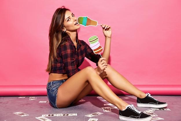Jonge mooie vrouw. trendy vrouw in casual zomer kleding zittend op de vloer in de buurt van roze muur. positief model dat rekwisieten zoet ijs en macaron eet.