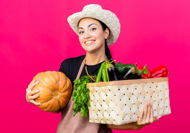 Jonge mooie vrouw tuinman in schort en hoed bedrijf krat vol groenten en pompoen lachend met blij gezicht