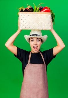 Jonge mooie vrouw tuinman in schort en hoed met mand vol groenten op haar hoofd glimlachend met blij gezicht staande over groene achtergrond