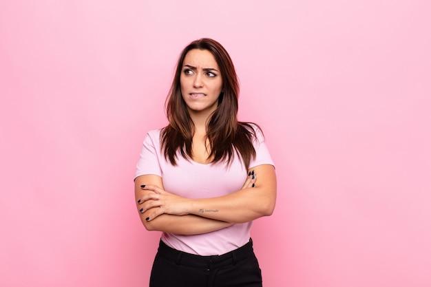 Jonge mooie vrouw twijfelen of denken, lip bijten en zich onzeker en nerveus voelen