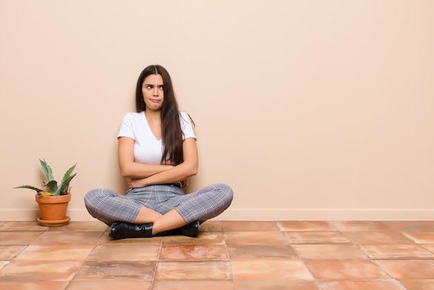 Jonge mooie vrouw twijfelt of denkt, lip bijt en voelt zich onzeker en nerveus, op zoek naar ruimte aan de zijkant zittend op een vloer