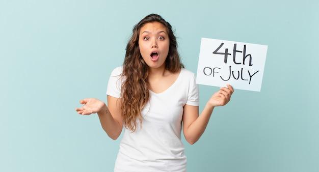 Jonge mooie vrouw verbaasd, geschokt en verbaasd met een ongelooflijk concept voor de onafhankelijkheidsdag van de verrassing