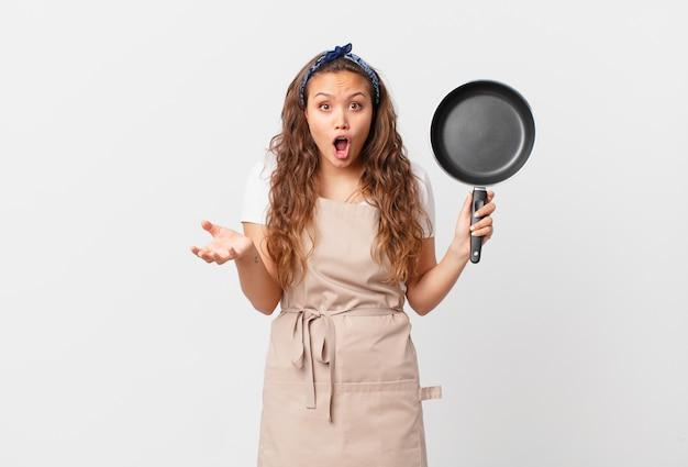 Jonge mooie vrouw verbaasd, geschokt en verbaasd met een ongelooflijk verrassingskoksconcept en een pan vasthoudt
