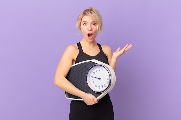 Jonge mooie vrouw verbaasd, geschokt en verbaasd met een ongelooflijke verrassing. dieet concept