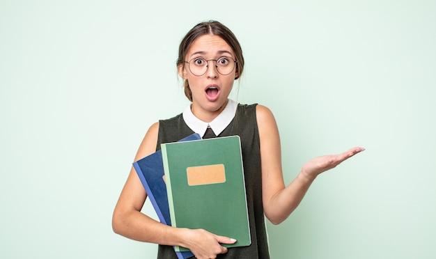 Jonge mooie vrouw verbaasd, geschokt en verbaasd met een ongelooflijke verrassing. universitair concept